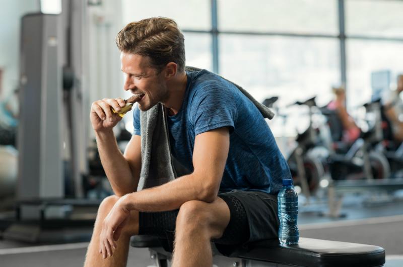 homme mangeant un snack en salle de sport